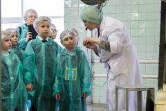 Маленькие экскурсанты узнают, как работает тубонаполнительная машина